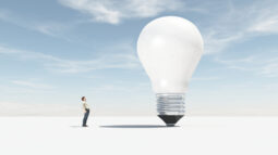 A man facing a giant lightbulb: Think big for Success Through Failure episode 296 Think Like Elon: Provocative Questions and Tactics for Unleashing Your Inner Greatness