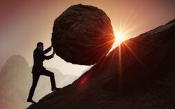 A man pushing a huge rock uphill (Success Through Failure episode 310: Should I Crush It Every Day? Or Get Off the War Path? How to Create Balanced Success)