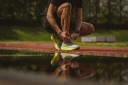A man tying his shoelace; getting ready to run (Success Through Failure episode 313: How to Leverage Two Laws of Persuasion Psychology To Trick Yourself Into Doing What You Don't Want To Do)