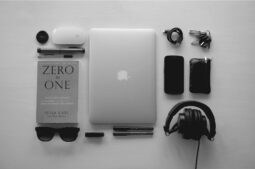 Gadgets like laptop, phone, headset, mouse, and a book (Success Through Failure episode 319: Jim's Favorite Books, Habits, and Gadgets For Consistency, Balance, and Success)