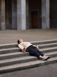 A lady lying on the stairs and holding a coffee (Success Through Failure episode 321: Get Unstuck: 5 Productive Pause Questions That Will Instantly Amplify Your Results)